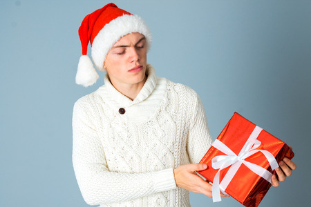 celebration smiley: serious guy with red gift in hands and in santa hat posing in studio