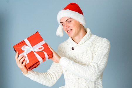 celebration smiley: portrait of happy young guy with gift box in hands and santa hat posing and smiling in studio