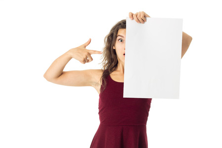 surprised young brunette girl in red dress with white placard in hands isolated