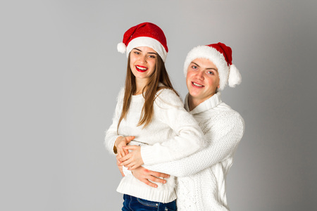 hat new year s eve: portrait of young cute couple celebrate christmas in studio on grey background
