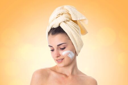beautiful Young girl takes care her skin with towel on head smeared with cream isolated on white background. Health care concept. Body care concept. Young woman with healthy skin.