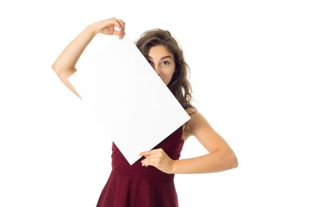 young pretty brunette girl in red dress with white placard in hands isolated