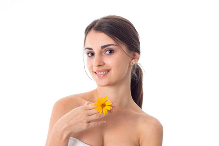 gorgeous girl takes care her skin with yellow flower in hands isolated on white background. Health care concept. Body care concept. Young woman with healthy skin. Stock Photo