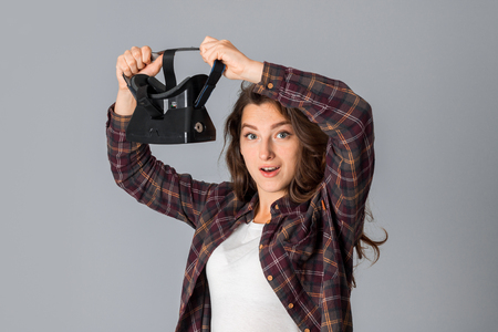 attractive brunette girl testing virtual reality glasses in studio on grey background Stock Photo