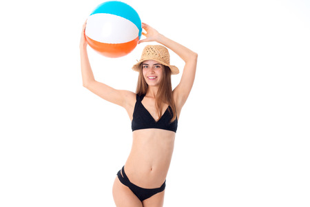 charming girl in black swimsuit with beach ball isolated on white background