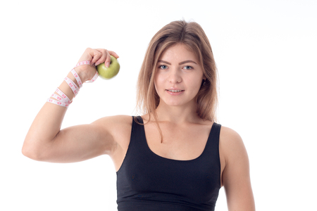 waistline: Beautiful athletic girl shows muscles clenching an apple in his hand and erase directly