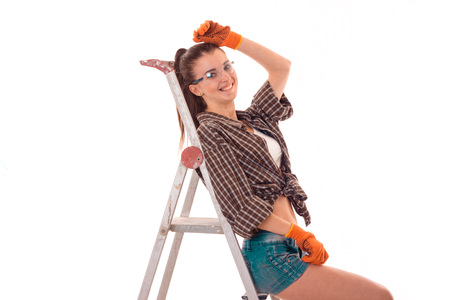 female sexuality: young charming builder girl in uniform makes renovation isolated on white Stock Photo