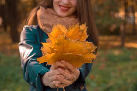 girl with red lips stretched in the hands of autumn leaves close-up Stock Photo
