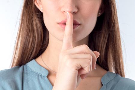 boca cerrada: Una chica que tiene un índice cerca de la boca cerrada Foto de archivo