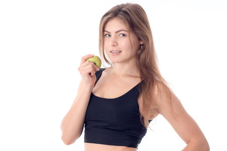 beautiful girl holding an apple in his hand and smiling looking forward the second hand on the side Stock Photo