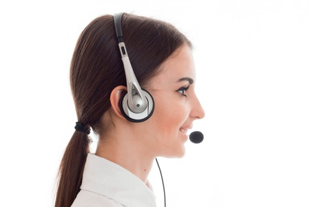 profile portrait of attractive brunette call center worker girl with headphones and microphone isolated on white Stock Photo