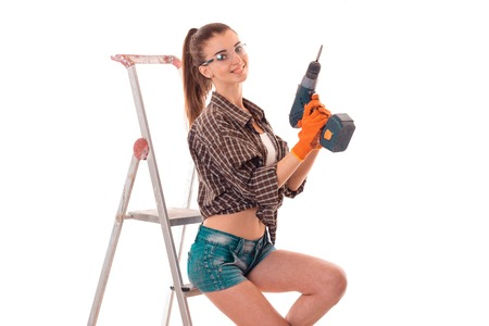 female sexuality: sexy brunette lady makes refurbish an apartment with drill in hands and ladder isolated on white background
