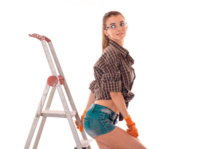 sexy brunette lady builder makes renovation isolated on white Stock Photo