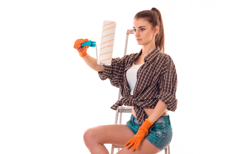 sexualidad: portrait of young attractive brunette builder girl makes renovation isolated on white