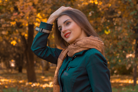 stands: beautiful girl with red lipstick stands in autumn Park and kept the ball for hair Stock Photo