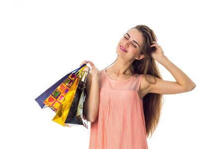 girl in a dress closed her eyes and holds in his hand a lot of different packages, isolated on white background