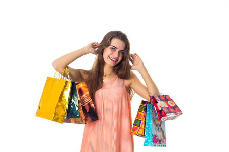 young girl raised in the hands of a beautiful bright bags with gifts and smiling isolated on white background