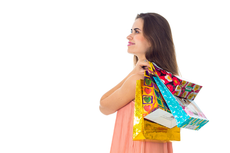 a young girl is worth turning sideways and keeps bright colored shoulder bags isolated on white background