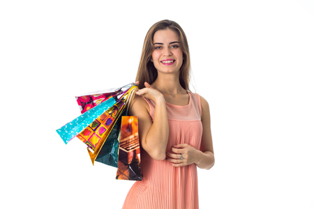 young girl stands up straight looks ahead and holds in his hand the different packages with gifts is isolated on a white background