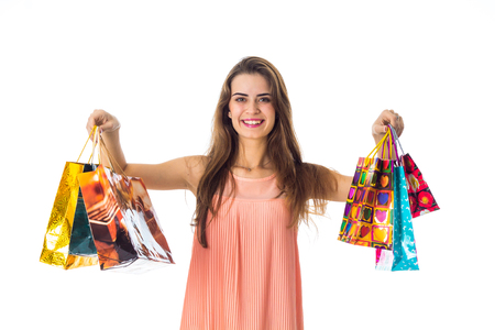 girl holding a different packages of shops looks straight and smiling isolated on white background Stock Photo