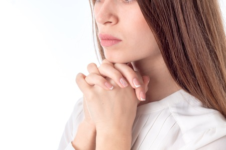 young girl crossed her fingers and palms near face