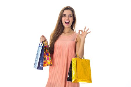 Merry girl holds many packages from stores isolated on white Reklamní fotografie