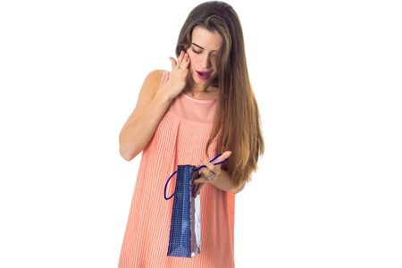 a young girl looks for a package with a gift isolated on white