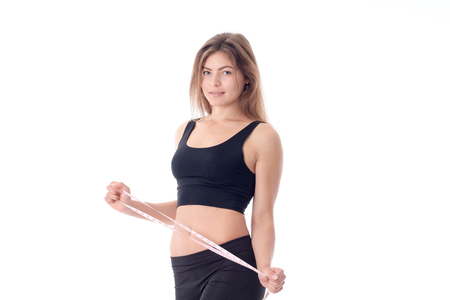 sports a slender girl in black tights and a top side which is holding a tape measure in his hand and smiling