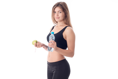 Beautiful slim girl in a black top and tights stands sideways and holds in one hand a green apple in the other hand a bottle of water. Stock Photo