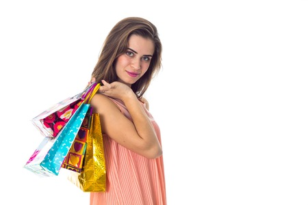 young serious girl stands sideways and holding a colored bags isolated on white