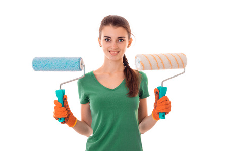 female sexuality: adorable young brunette lady makes renovation in gloves with paint roller in her hands smiling on camera isolated on white Stock Photo
