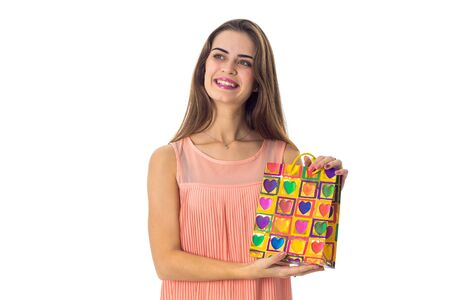 girl raised in the hands of the color package with shopping is isolated on a white background