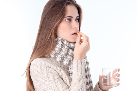 a girl in a scarf worth sideways and drinking the Tablet is isolated on a white