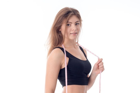 close-up of young sexy athletic girl who is standing sideways and looking directly holds a tape measure stretched her across the neck