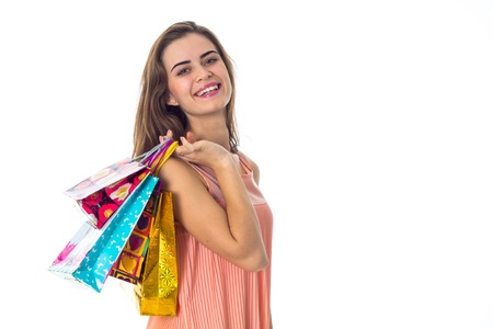christmas spending: smiling girl holding on his shoulder gift bags isolated on white