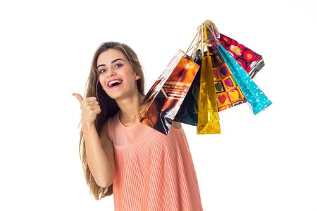 girl raised in hand many colored different gift packages and shows the class of isolated on white background