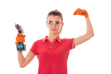 female sexuality: beauty young brunette builder girl in uniform and glasses makes renovation with drill in hands isolated on white Stock Photo