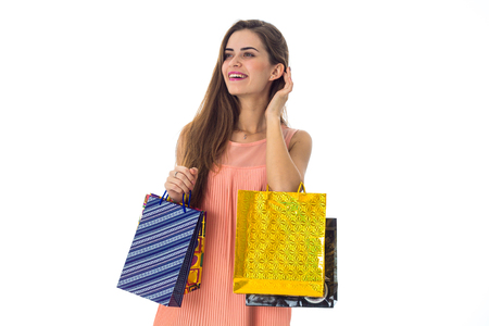 young girl with shopping looks toward isolated on white