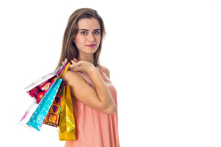 a young girl stands sideways and holding a colorful shopping bags isolated on white Stock Photo