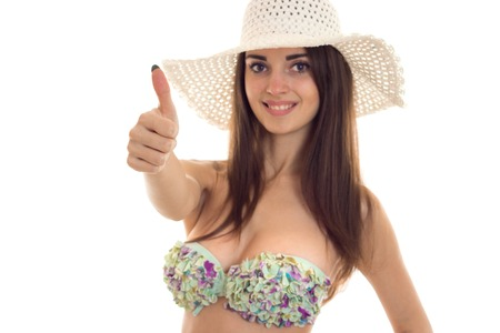 happy slim young lady with big natural breasts in swimsuit with floral pattern and straw hat with wide brim smiling and showing thumbs up isolated on white.