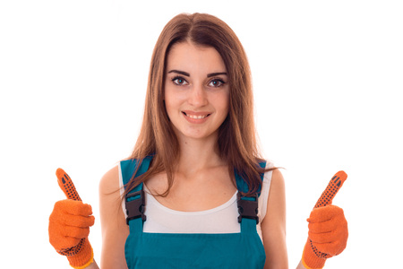 female sexuality: cheerful young slim builder girl makes renovations in gloves isolated on white