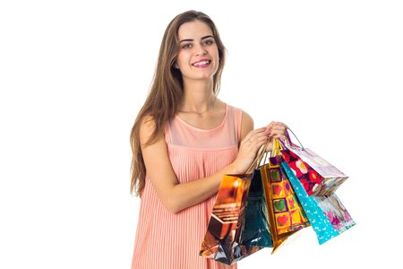 a cheerful young girl keeps itself the gift bags isolated on white Reklamní fotografie