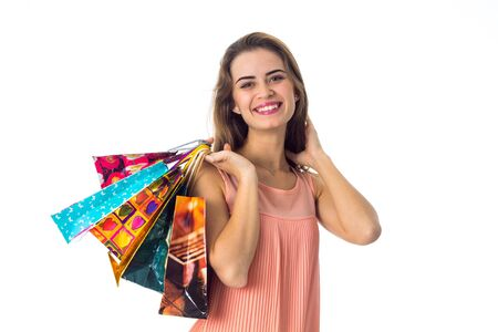 good beautiful girl holds in his hand a lot of colorful packages with purchases isolated on white