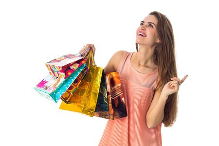 Merry girl looks up and holding a colorful shopping bags isolated on white