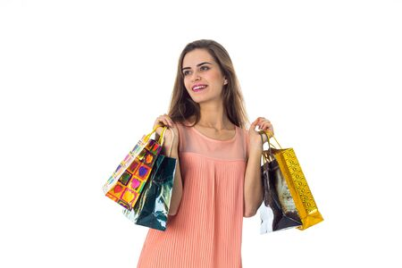 the girl looks to the side and holds the two hands of different colored bags isolated on white
