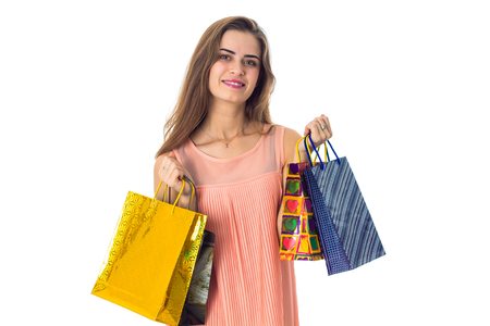 a young girl stands up straight and keeps on hand a bright bags isolated on white