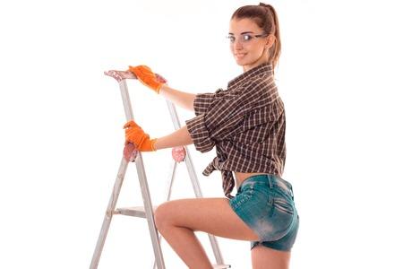 Porträt der jungen sinnlichen Brunette-Gebäudefrau mit Leiter bildet Erneuerung und lächelt auf der Kamera, die auf Weiß lokalisiert wird