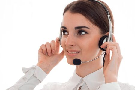 attractive young business woman working in call center with headphones and microphone looking aside and smiling isolated on white