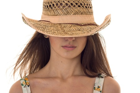 close up portrait without eyes of beautiful young brunette woman with straw hat posing isolated on white Stock Photo