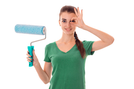 a young girl in a green t-shirt holding a roller to paint walls isolated on white